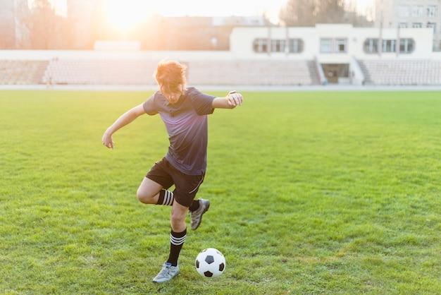 Jovem desportista atirando bola de futebol