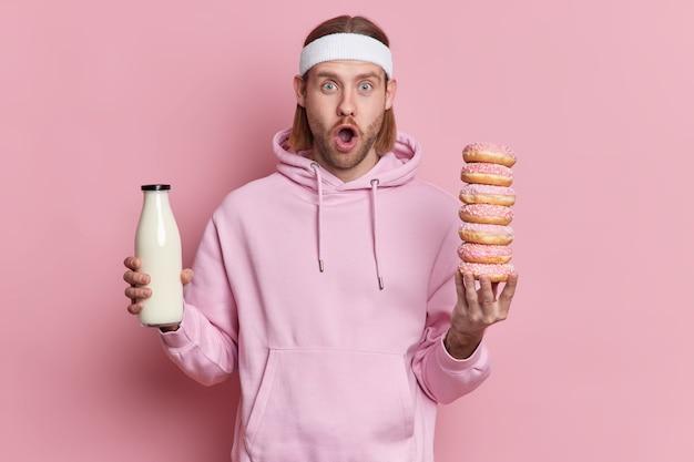 Jovem desportista barbudo chocado tem a tentação de comer olhares de junk food com a boca bem aberta. um cara esportivo usa um capuz e uma fita na cabeça com uma garrafa de vidro de leite e muitos donuts doces