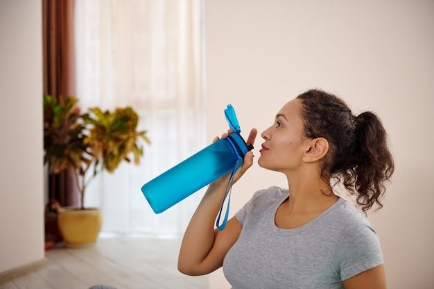 Jovem desportista bebendo água após treino desportivo. conceito de reidratação