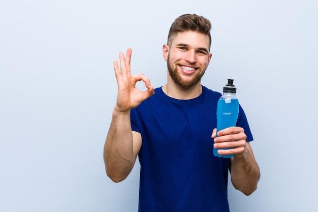 Jovem desportista caucasiana segurando uma bebida isotônica alegre e confiante mostrando o gesto ok.
