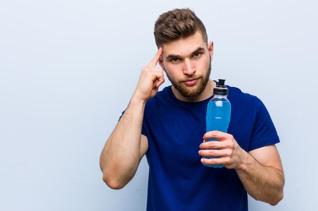 Jovem desportista caucasiana segurando uma bebida isotônica, apontando seu templo com o dedo, pensando, focado em uma tarefa.