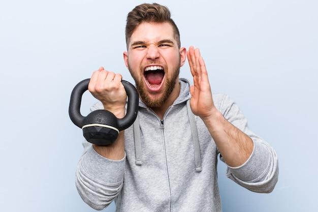 Jovem desportista caucasiano segurando um haltere gritando animado para a frente.