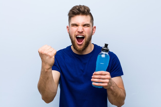Jovem desportista caucasiano segurando uma bebida isotônica torcendo despreocupado e animado. conceito de vitória.