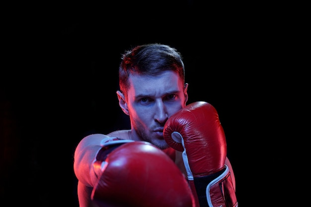 Jovem desportista com luvas de boxe acertando o rival à sua frente enquanto lutava