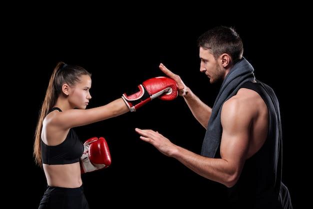 Jovem desportista com roupa desportiva e luvas de boxe, exercitando-se com o treinador, consultando-a sobre as regras de luta
