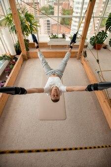 Jovem desportista com roupa desportiva pendurado no chão com os braços e as pernas presos a cordas durante o treino individual de ioga aérea