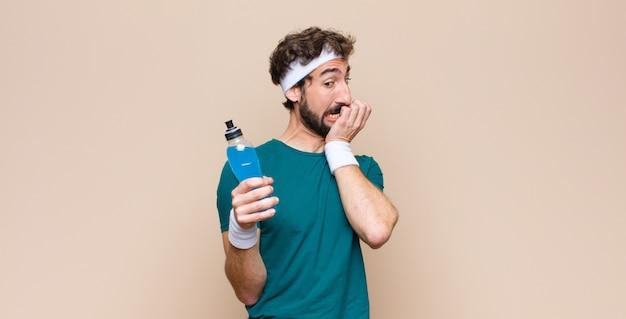 Jovem desportista com uma garrafa de bebida energética contra uma parede plana