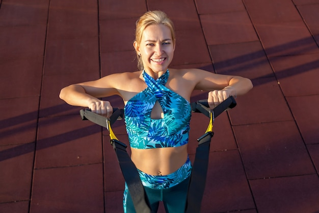 Jovem desportista está envolvida pela manhã em um campo de esportes. exercícios de fitness com loops. estilo de vida saudável.