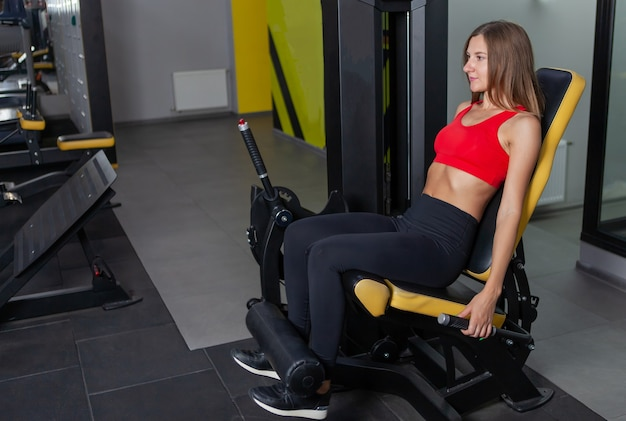 Jovem desportista fazendo exercícios de fitness para os músculos das pernas em uma academia moderna