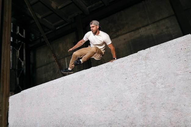 Jovem desportista fazendo parkour na cidade. atleta está praticando corrida livre ao ar livre nas ruas