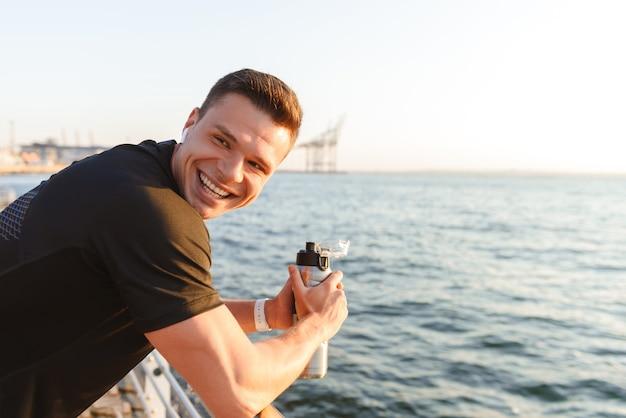 Jovem desportista feliz com fones de ouvido segurando uma garrafa de água