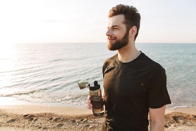 Jovem desportista feliz segurando uma garrafa de água