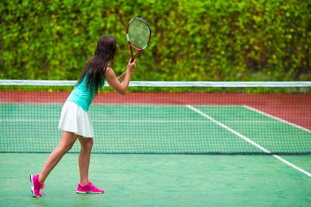 Jovem desportista jogando tênis de férias tropicais