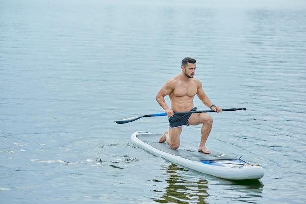 Jovem desportista mantendo longo remo, de pé sobre um joelho, nadando a bordo de sup no lago da cidade.