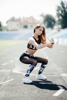Jovem desportista muito bem construída, olhando propositadamente para a frente e diligentemente fazendo agachamentos com elástico no estádio ao ar livre