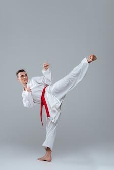 Jovem desportista na prática de quimono no caratê isolado sobre fundo cinza. olhando para o lado.
