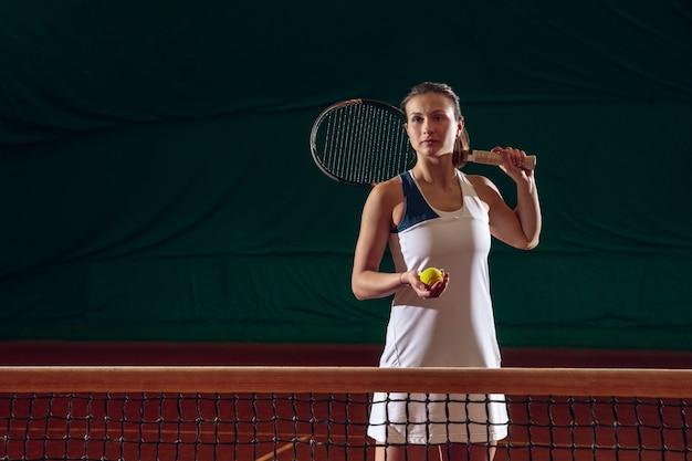 Jovem desportista profissional caucasiana jogando tênis na parede da quadra de esportes. treinar, praticar em movimento, ação. força e energia. movimento, anúncio, esporte, conceito de estilo de vida saudável. vista frontal.