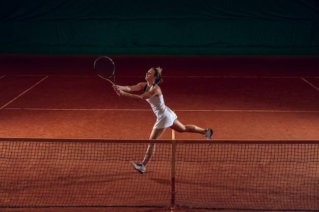 Jovem desportista profissional caucasiana jogando tênis na quadra de esportes. treinar, praticar em movimento, ação. força e energia. movimento, anúncio, esporte, conceito de estilo de vida saudável. maior ângulo.