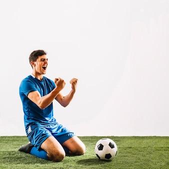 Jovem desportista, regozijando-se sobre a vitória no campo
