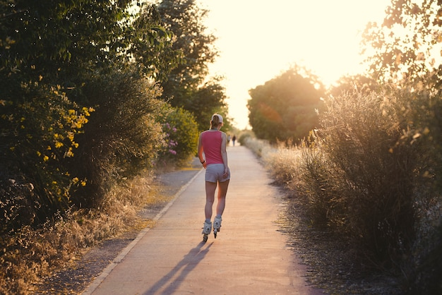 Jovem desportista se divertindo enquanto patina durante o pôr do sol