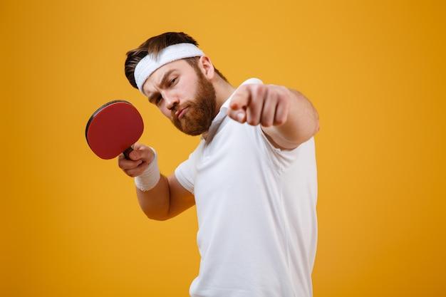 Jovem desportista segurando a raquete para tênis de mesa enquanto aponta.
