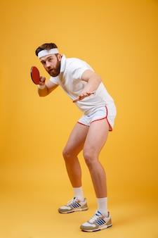 Jovem desportista segurando a raquete para tênis de mesa.