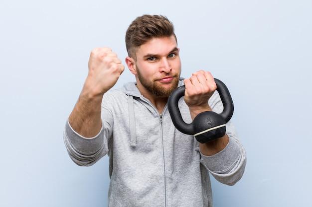 Jovem desportista segurando um haltere mostrando o punho para a câmera, expressão facial agressiva