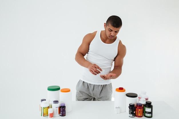 Jovem desportista segurando vitaminas e comprimidos de esporte.