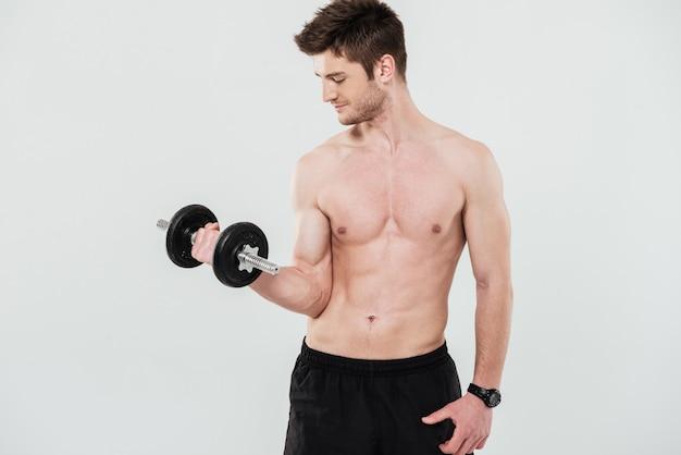 Jovem desportista sem camisa, fazendo exercícios com um haltere