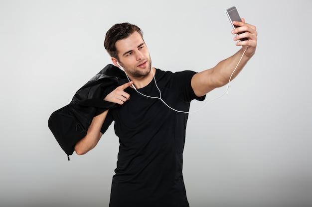 Jovem desportista sério fazer selfie com saco por telefone celular