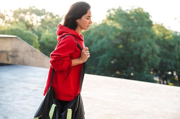 Jovem desportista sorridente com um moletom e caminhando ao ar livre, carregando uma sacola esportiva