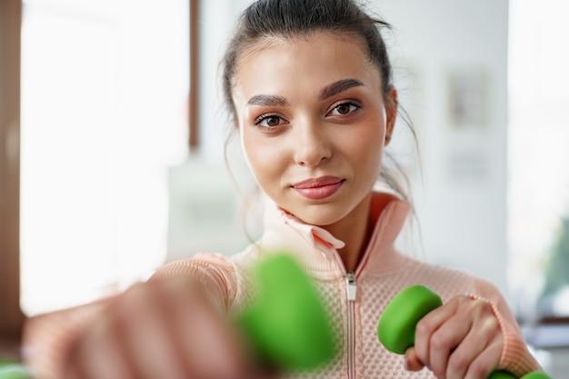 Jovem desportiva a fazer exercício em casa com halteres