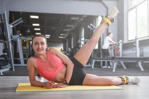 Jovem desportiva alegre desfrutando de se exercitar na academia, levantando as pernas com pesos nos tornozelos