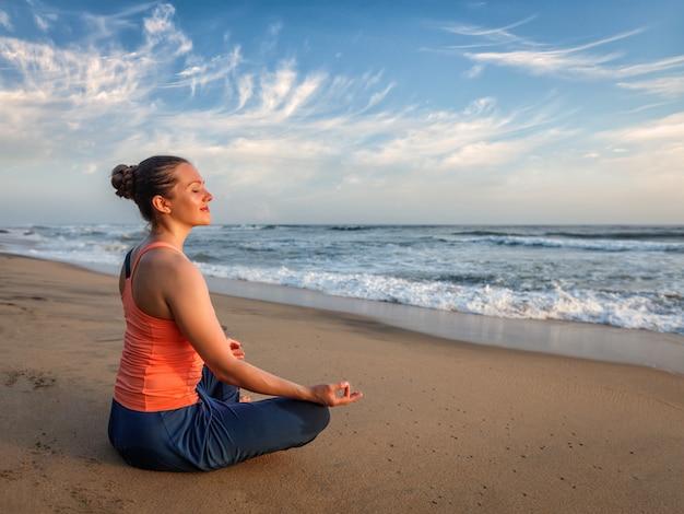 Jovem desportiva cabe mulher fazendo ioga oudoors na praia