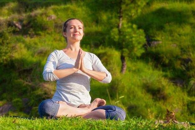 Jovem desportiva cabe mulher fazendo yoga pose de lótus oudoors