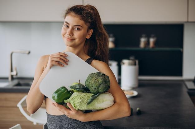 Jovem desportiva com balança e legumes na cozinha