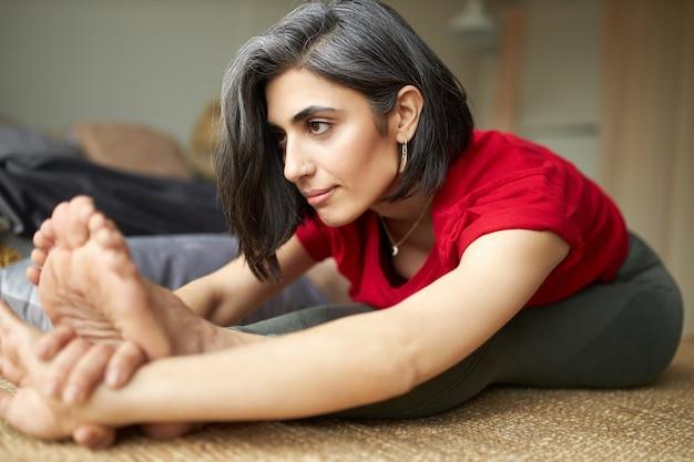 Jovem desportiva com cabelos grisalhos praticando hatha ioga em casa, fazendo paschimottanasana