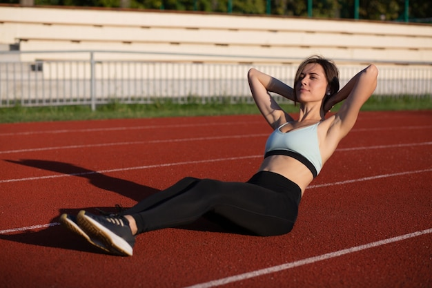 Jovem desportiva com roupa de fitness a fazer abdominais