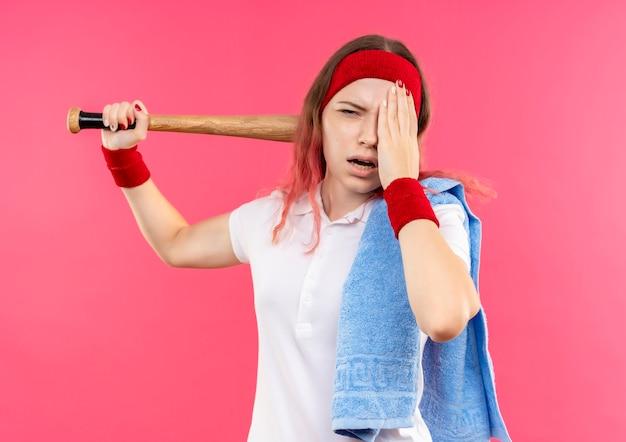 Jovem desportiva com uma bandana na cabeça e uma toalha no ombro, segurando um taco, parecendo cansada e exausta em pé sobre a parede rosa