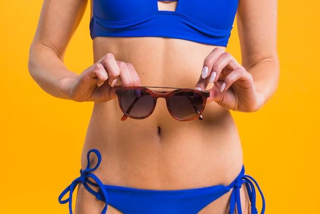 Jovem desportiva em trajes de banho, mantendo os óculos de sol