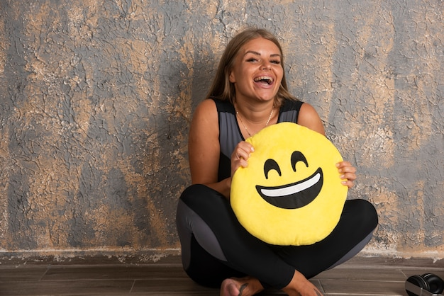Jovem desportiva em trajes desportivos, segurando uma sorridente almofada de emoji abaixo.