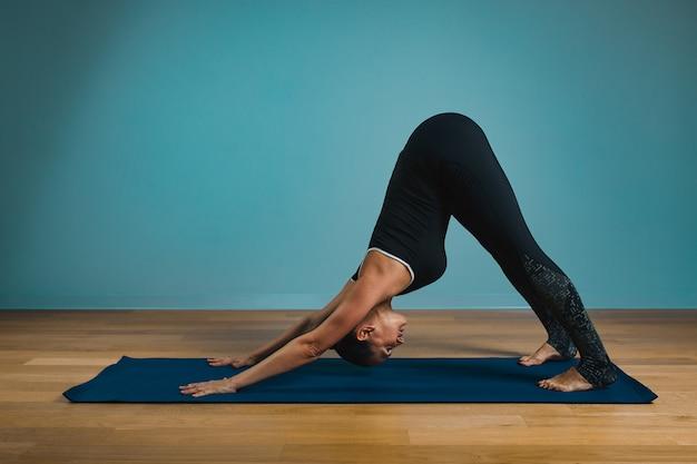 Jovem desportiva fazendo alongamento. menina magro praticando ioga dentro de casa, sobre fundo azul. calma, relaxe, conceito de estilo de vida saudável.