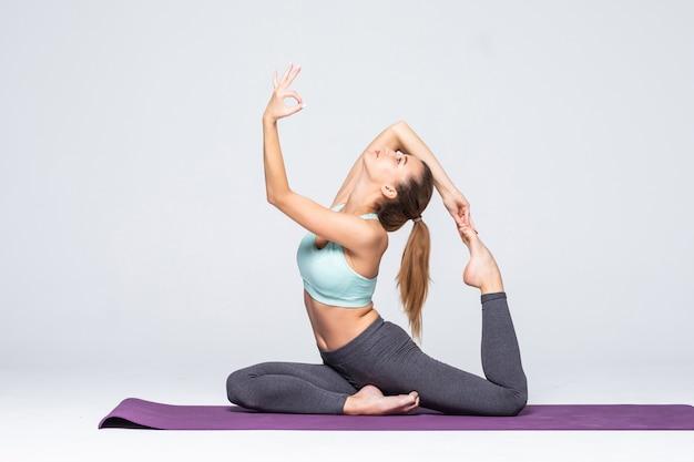 Jovem desportiva fazendo ioga isolada - conceito de vida saudável e equilíbrio natural entre o corpo e o desenvolvimento mental