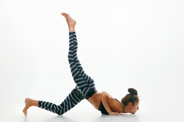 Jovem desportiva fazendo ioga isolada no branco