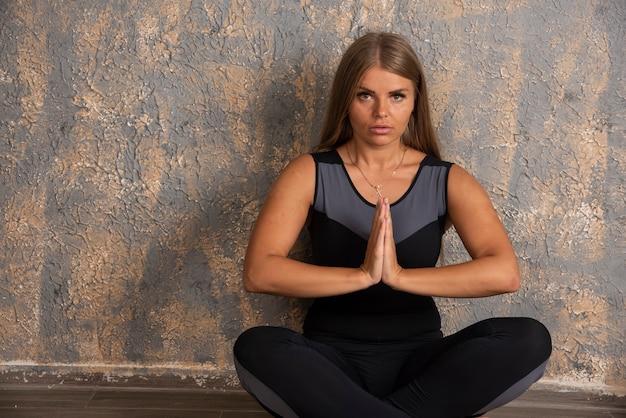Jovem desportiva fazendo meditação.