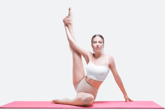 Jovem desportiva fazendo prática de ioga. ela se senta em um tapete vermelho com a perna para cima. mídia mista Foto Premium