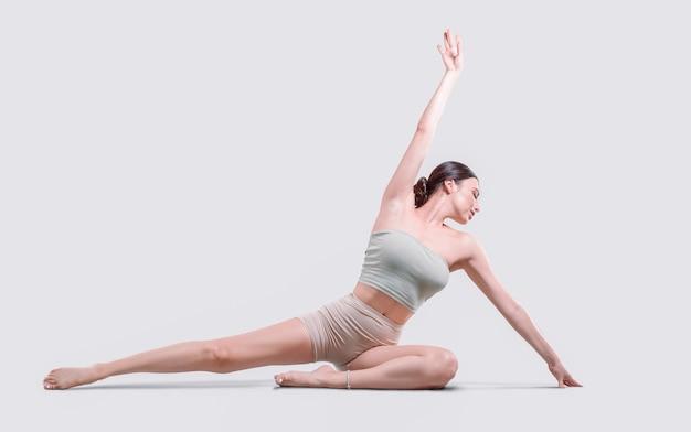 Jovem desportiva fazendo prática de ioga. ela se senta no tapete e se alonga. isolado em um fundo branco. mídia mista