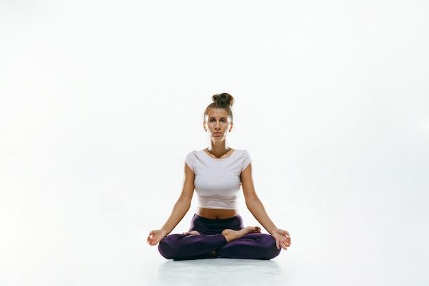 Jovem desportiva fazendo prática de ioga isolada. ajuste o modelo feminino flexível praticando. conceito de estilo de vida saudável e equilíbrio natural entre o desenvolvimento corporal e mental.