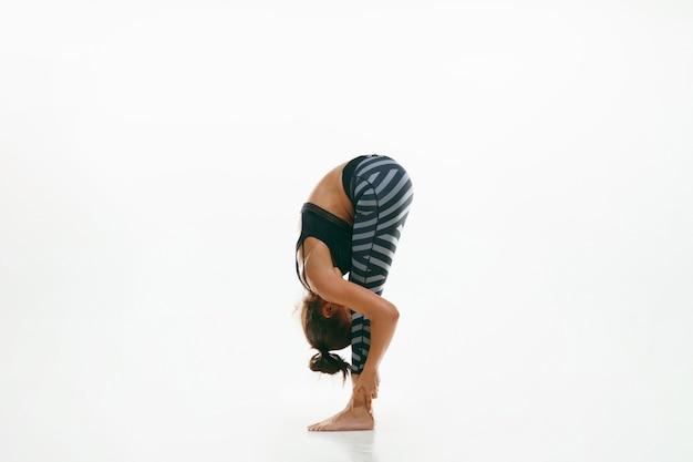 Jovem desportiva fazendo prática de ioga isolada na parede branca. ajuste o modelo feminino flexível praticando. conceito de estilo de vida saudável e equilíbrio natural entre o desenvolvimento corporal e mental.