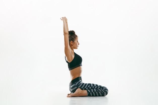 Jovem desportiva fazendo prática de ioga isolada no espaço em branco. modelo feminino flexível apto praticando